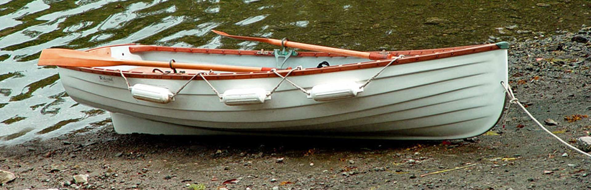Small rowboat landed on the shore by a lake.