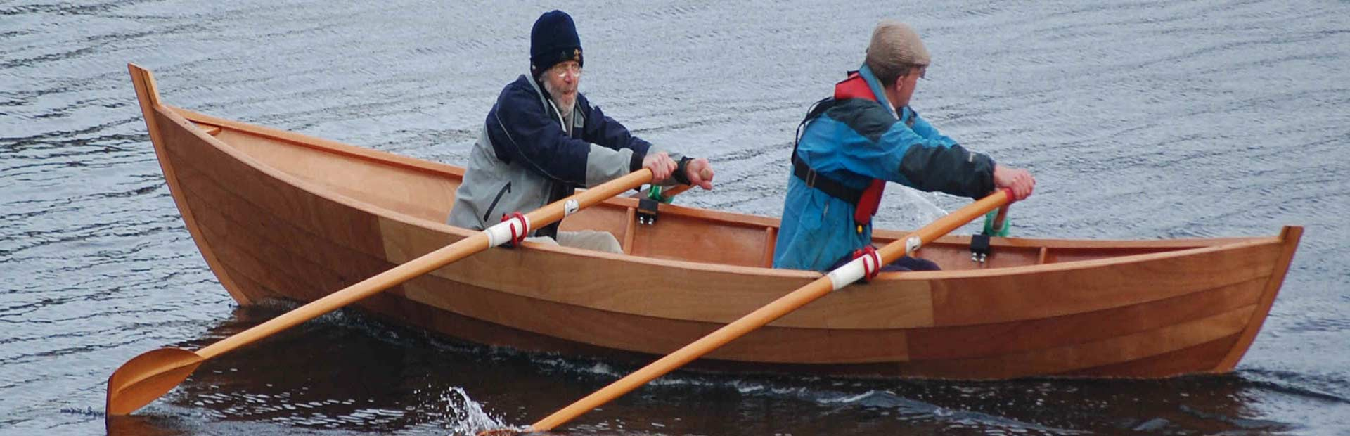Two men in wooden rowboat on a lake, rowing.