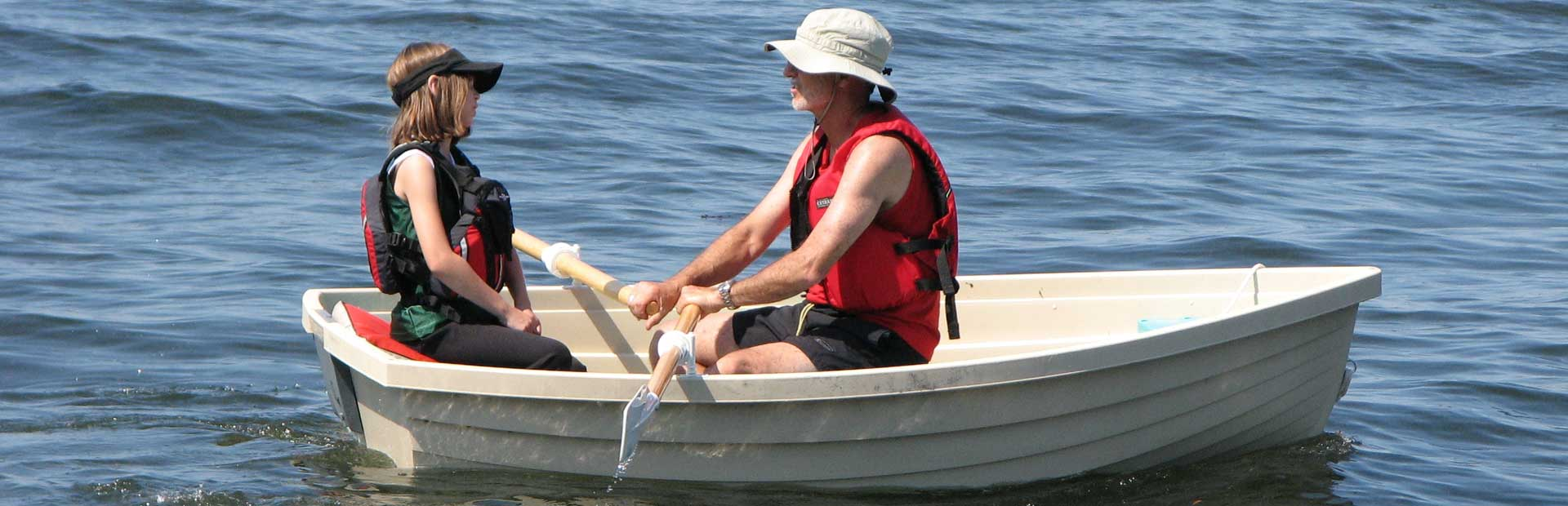 Father and daughter in small rowboat on a lake as Father rows.