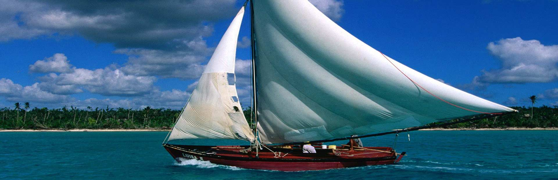 Beautiful wooden sailboat with sails catching the wind on shallow ocean waters by island shore.